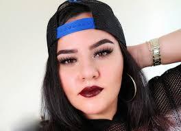 najla kaddour wearing a snapback hat backwards