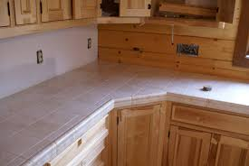 white beige tile countertop light brown wooden cabinets