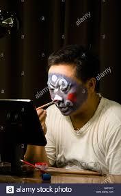 a beijing opera performer applies makeup stock image