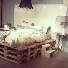 LAYERED PALLET FRAME BED WITH A WHITE TILE BACKGROUND SERVING AS A HEADBOARD