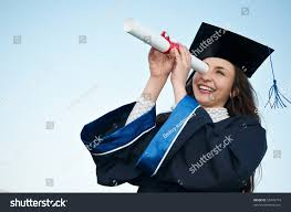 young laughing graduate girl student gown stock photo  young laughing graduate girl student in gown looking through diploma outdoors