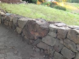 picture of how to build a natural dry stacked stone free standing or retaining rock wall
