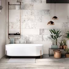 a chic modern space with neutral tiles a free standing bathtub on copper legs