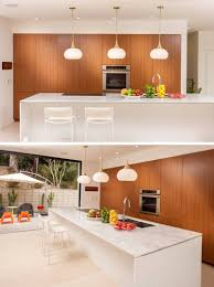in the kitchen three pendant lights anchor the mostly white kitchen island and wooden cabinetry adds a natural touch to the space