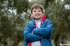 portrait of a cute boy standing with arms crossed smiling looking at the camera