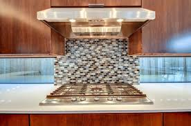 A Unique Kitchen With Glossy White Formica Countertops And A Glass Tile  Mosaic Behind The Range