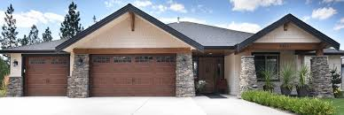 outside of a house with a brown garage door and beautiful stone pillars holding up the