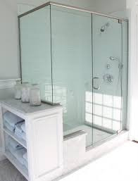 beach cottage bathroom with pale blue glass shower tile in brick pattern with carrara marble shower bench and white carrara penny tile shower floor