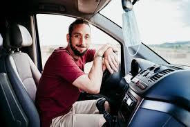 man wearing face mask sitting in car
