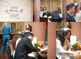 bride and groom signing marriage license paperwork in the hall of records of santa barbara courthouse