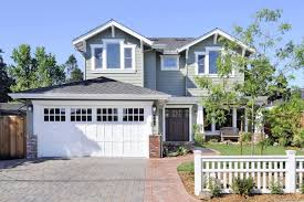 white garage door glass garage window trellis woden siding grey roof brick paving wall lamps craftsman