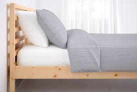 IKEA TARVA single bed frame in solid untreated pine wood made up with white  sheets and