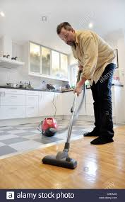 Kitchen Floor Vacuum Middle Aged Man Using A Vacuum Cleaner On The Kitchen Tiled Floor