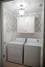 Grey stenciled laundry room with wallpaper wainscoting. The after photo of  my laundry room thanks