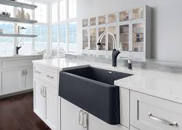 this black farmhouse sink is in direct contrast to the counter and cabinets making it a bold statement piece