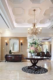 walnut round table flower arrangement iron chandelier front dark stained wooden chest silver rectangular mirror rustic