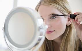 woman putting on mascara in mirror