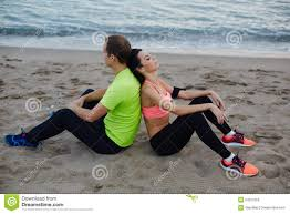 Fit woman and man <b>dressed</b> in <b>fluorescent</b>-shirt taking break after run