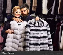 woman with smiling face in black fur coat with bearded man couple ping concept couple in love holds white sable and
