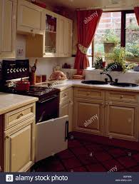 Small Fitted Kitchen Double Circular Sinks Below Window With Red Curtains In Small