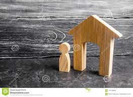 Real Estate Renting A Wooden Figure Of A Man Stands Near A Wooden House On A Gray