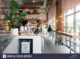 Hostesses Talking Looking At Seating Chart In Restaurant