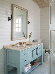 This is the perfect summer house bathroom with shiplap walls, a weathered  wooden mirror with