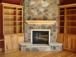 interior grey stone fireplace base added by brown wooden mantel shelf and black metal fire