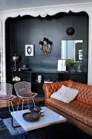 a dark alcove with 3 chic light sources bertoia chairs a cognac leather chesterfield chesterfield sofa leather 3