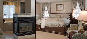 wing chair jacuzzi tub with window above behind three sided gas fireplace king bed