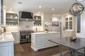 beautiful kitchen features open display cabinets with interior painted dark gray over ivory cabinets paired with white marble countertops and a subway tiled