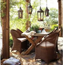 contemporary lantern pendant lamps above rustic outdoor dining table with brown rattan armchairs set on stoned charming outdoor furniture design