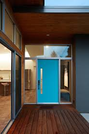 blue door house. The Electric Blue Door Of This House Is Framed By Glass Windows, Making Entrance Modern Home Look Larger.