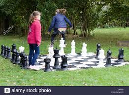garden chess set. Children Playing On A Giant Garden Chess Set