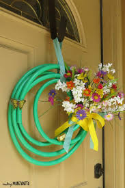 summer wreath made with a garden hose bright ribbon and colorful faux flowers hanging on