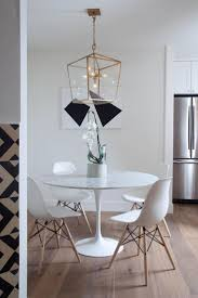 minimalist dining furniture design. white eamesstyle dining chairs surround the contemporary round table in this minimalist furniture design i