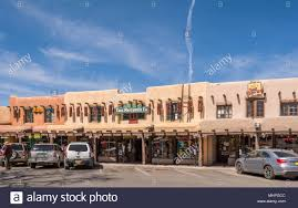tourist s with adobe style architecture in historic taos plaza taos new mexico