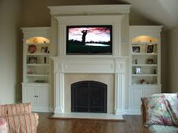 beautiful white fireplace surrounds with bookcases along with large tv set and some pictures