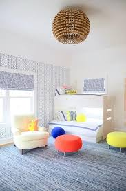 contemporary boys bedroom is illuminated by a wood beehive chandelier hung over a blue rug complementing an accent wall covered in serena lily feather