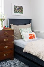 navy blue twin bed with wood campaign dresser as nightstand