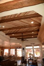 open plan home s ceiling design created with real wood planks and faux beams combined