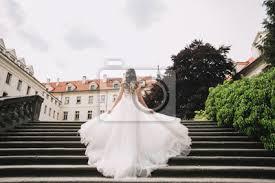 Hier findest du alle liebevoll getragene brautkleider, die nun auf eine zukünftige braut warten, die sie beglücken dürfen. Die Braut In Einem Schonen Flatternden Brautkleid Auf Der Treppe Fototapete Fototapeten Schone Flattern Tschechisch Myloview De