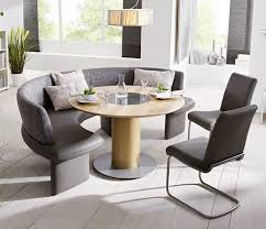 grey upholstered curved bench with round table and chair placed on wooden floor