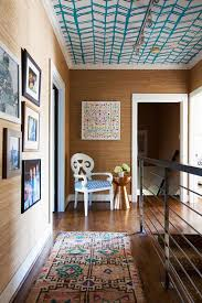 wallpapered ceiling and grasscloth walls with moroccan rug in hallway landing house tour via coco