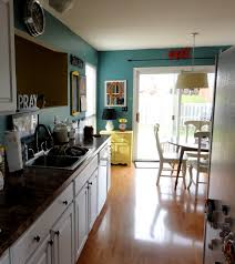 blue kitchen wall paint plus white wooden cabinet with black counter top and sink placed on