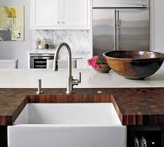 end grain butcher block surrounds a farmhouse sink in a kitchen by christine julian and
