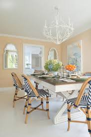 room is lit by an arteriors durango 8 light chandelier hung over a two tone x based dining table surrounded by serena lily chevron riviera side chairs