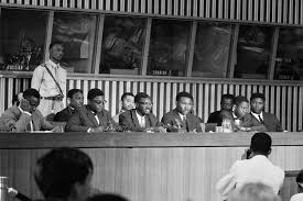 shown here flanked by colleagues prime minister lumumba third from left at desk answers questions during a press conference at