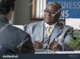 african american banker at his desk helping his client with a business loan