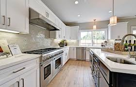 traditional kitchen with white cabinets quartz and glass subway tile